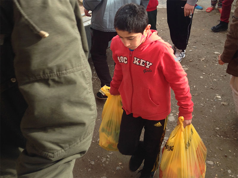 Young boy carrying heavy bags of aid