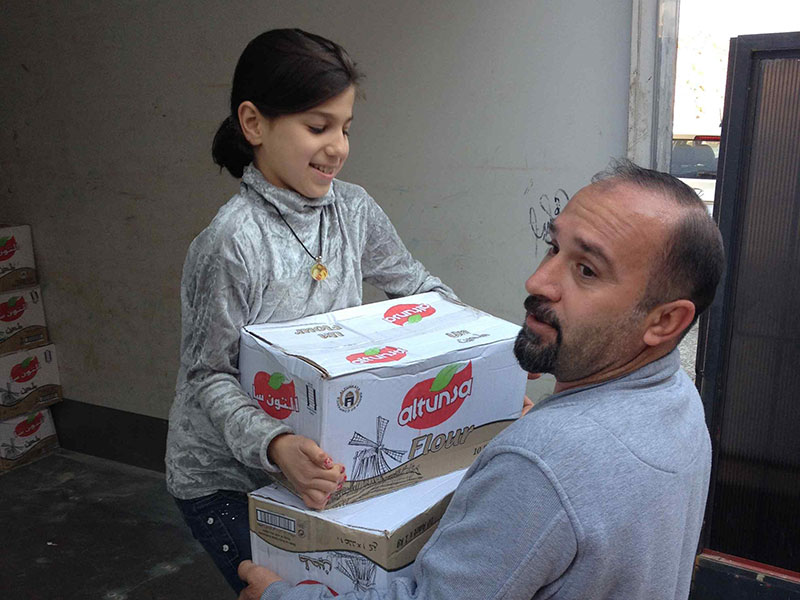 Iraqi child helping to pack aid