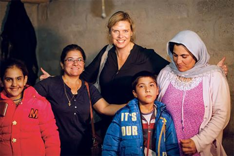 Charmaine Hedding stands in northern Iraq with refugees who fled from ISIS.